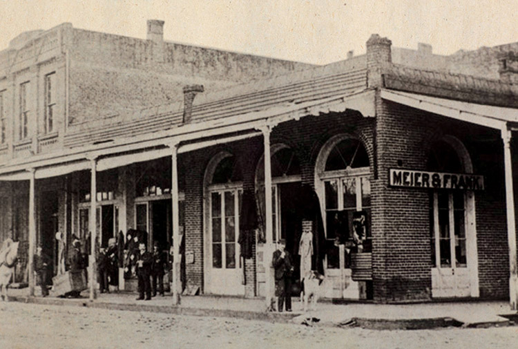 "Historic black-and-white photograph shows a wide, shaded storefront from the mid-1800s with a sign in front reading ""Meyer & Frank"""