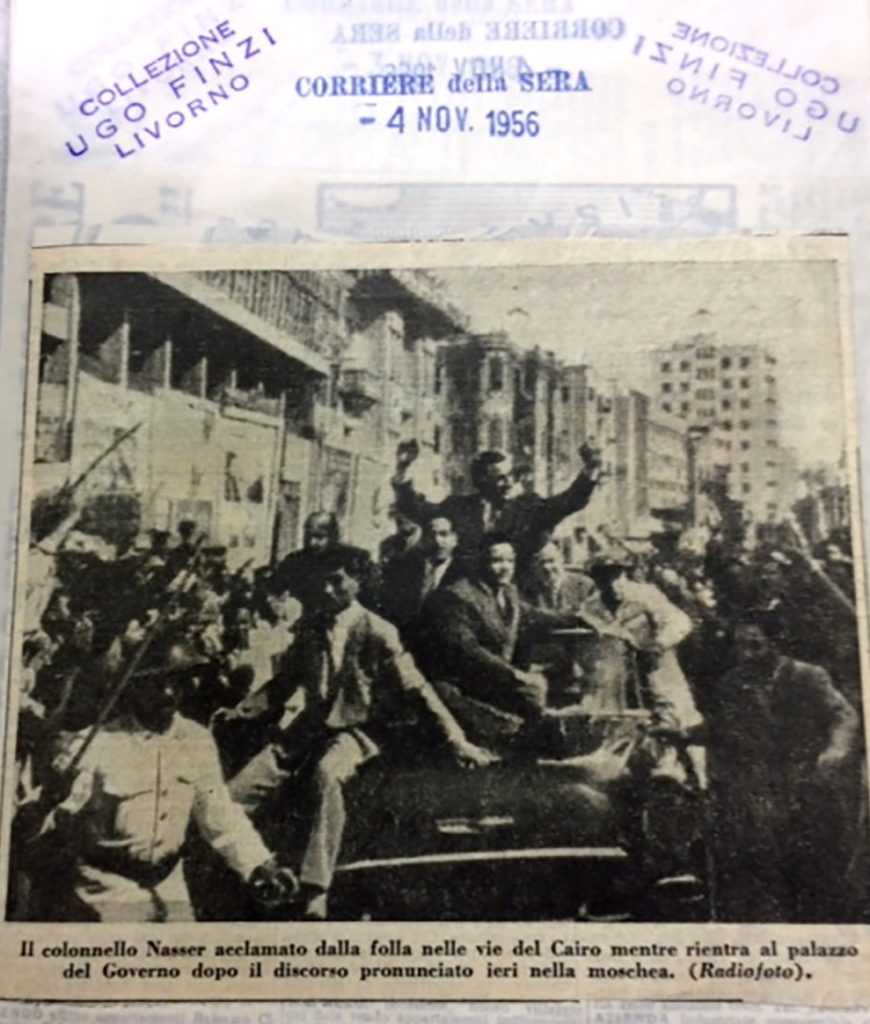 "An aged newspaper clipping shows a black-and-white photo of Nasser and a group of other men in suits riding through a crowded street on a car, surrounded by military guards on one side and cheering people on the other. Nasser stands and raises his arms victoriously. Stamps from the archivist read, ""Corriere della Sera, 4 November 1956, Collezione Ugo Finzi Livorno"""