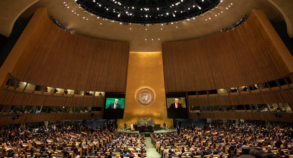 Donald Trump's image appears on the television screens in the grand, full wood-paneled U.N. assembly hall