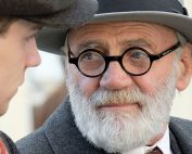 Film still showing actor Bruno Ganz as Sigmund Freud, wearing round spectacles, a hat and coat