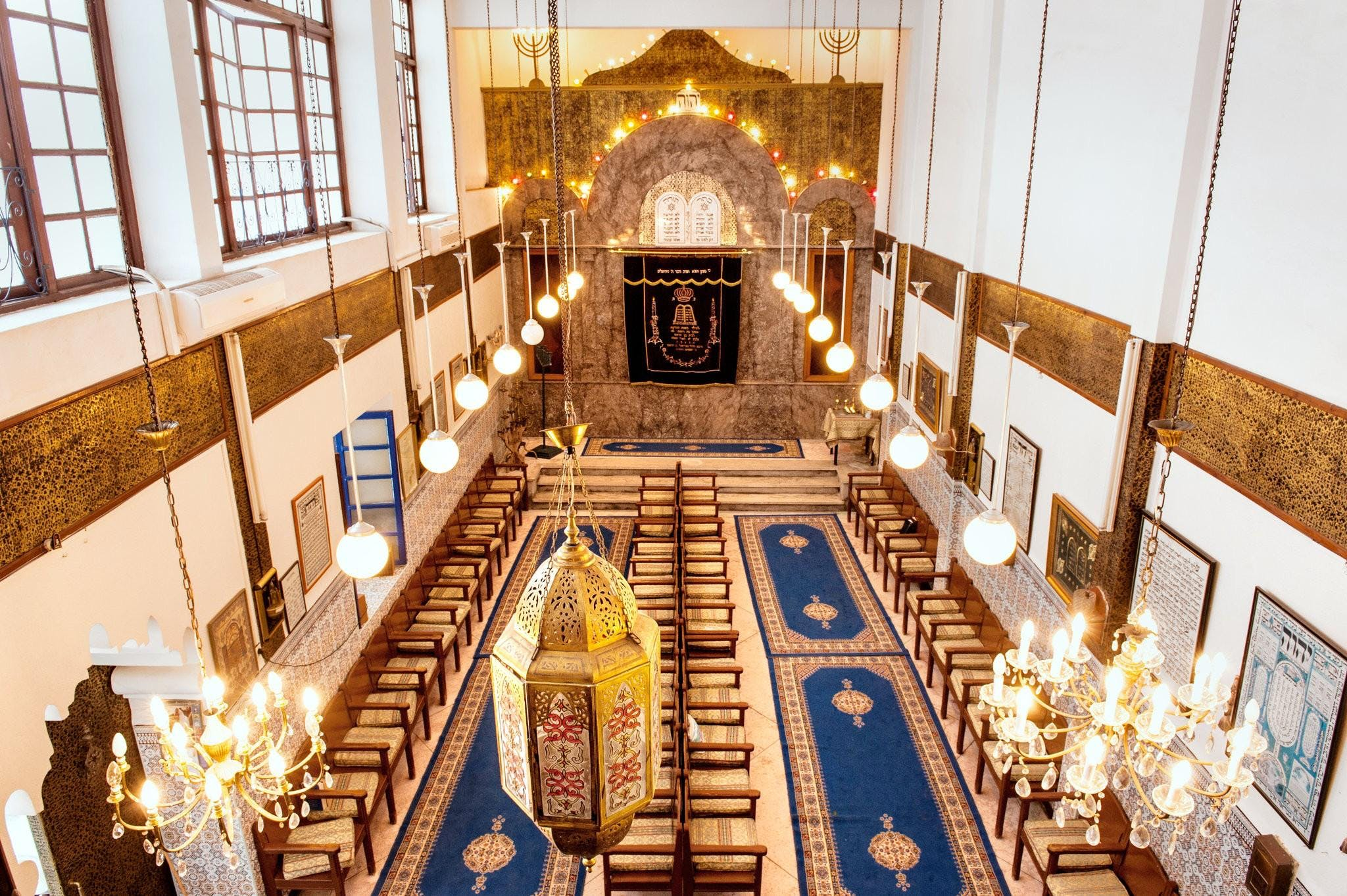 Synagogue in Marrakesh as seen from above. A row of round lanterns leads to the front of the room.
