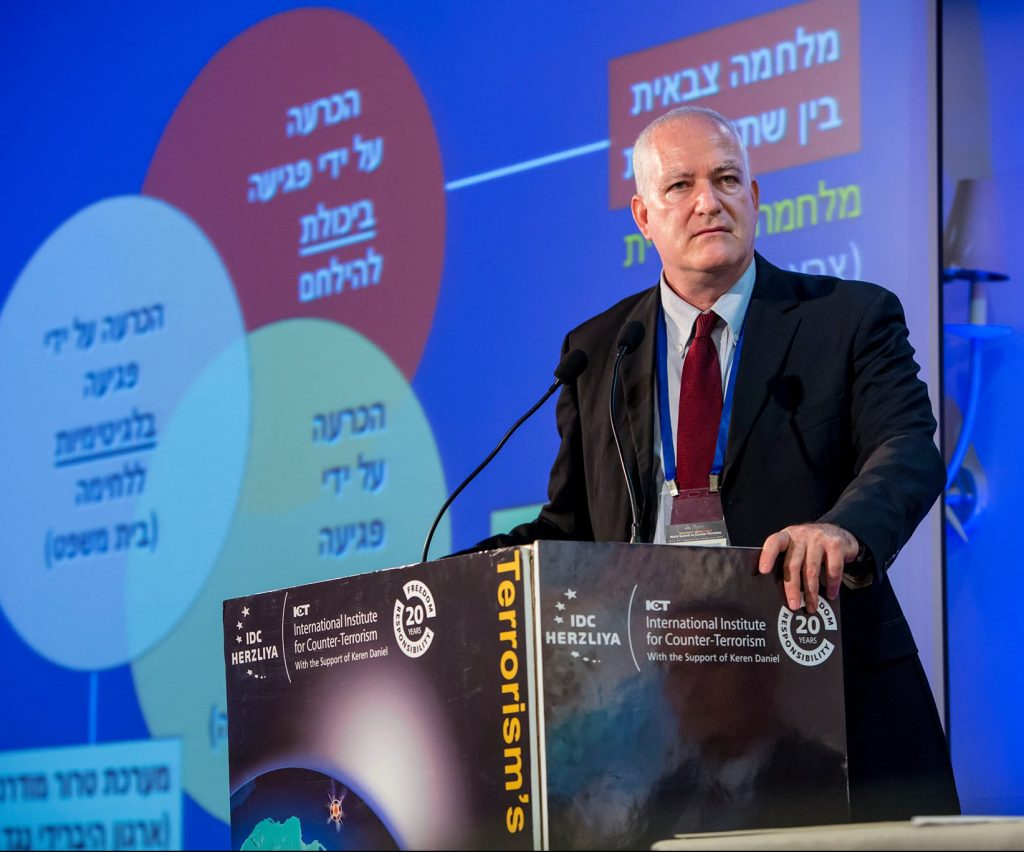 "A serious-looking man with white hair in a suit and tie stands at a podium reading ""International Institute for Counter-Terrorism."" A slide with Hebrew text is projected behind him."