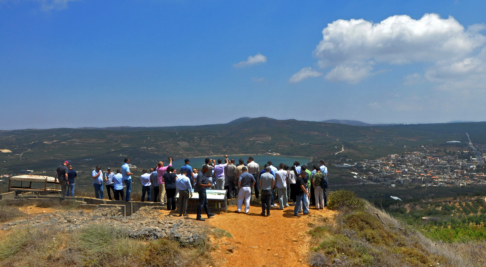 A group of people looks down over a green landscape with low hills and a small body of water, a small city visible at the side, a wide blue sky overhead.