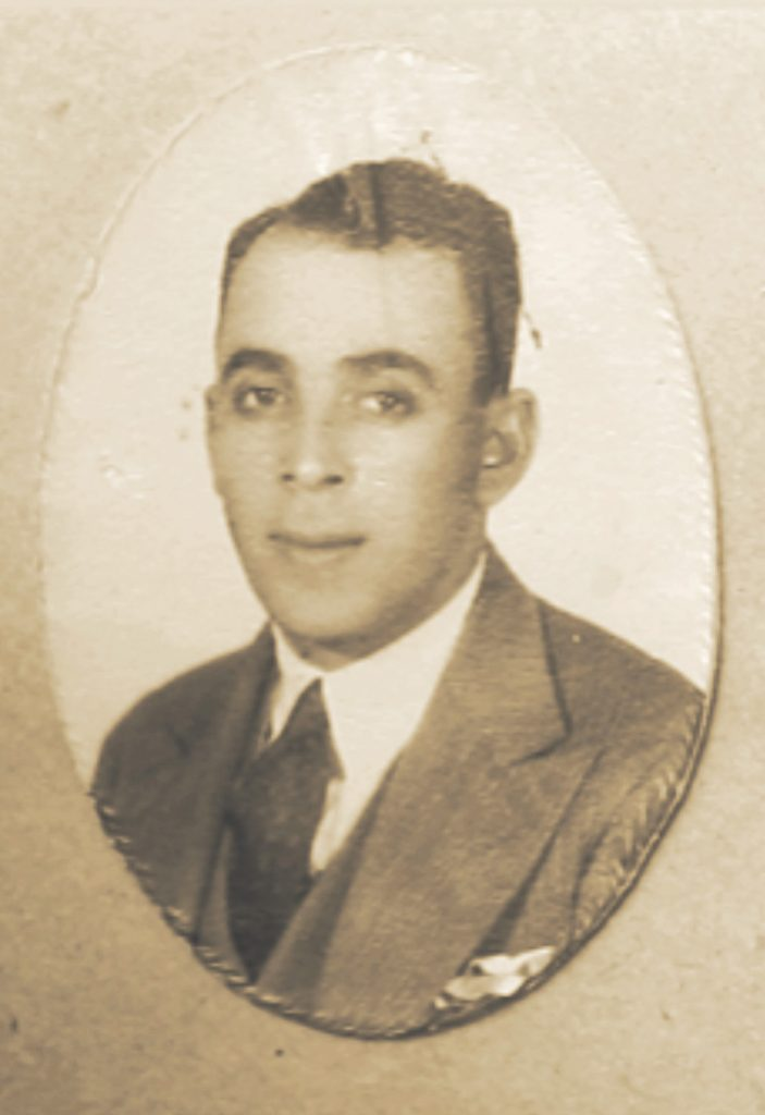 Black-and-white photographic portrait shows a young Mauricio Fresco wearing a suit and tie with slicked-back hair, smiling mildly