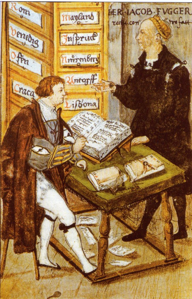 A printed illustration in color shows two men in medieval clothing, the younger one seated at a table writing in a book with a quill pen, the older standing above, consulting.