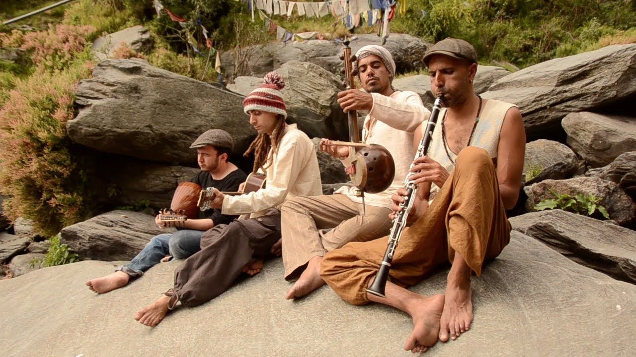 Four men sit on a rock with bare feet, playing instruments; prayer flags and brush are visible in the background