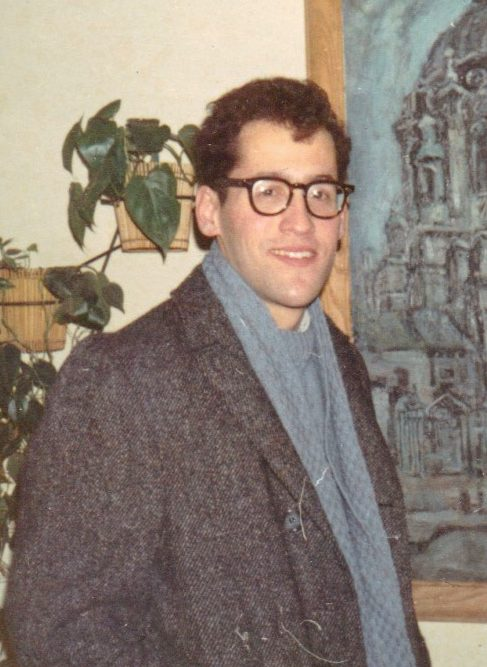 A color photograph of young Joe Butwin, wearing a coat, scarf and glasses, smiling, standing next to a painting and a plant