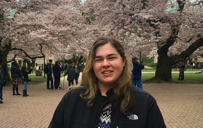Portrait of Jacqueline Goodrich smiling, in a dark coat and blouse, the UW quad and cherry blossoms in the background