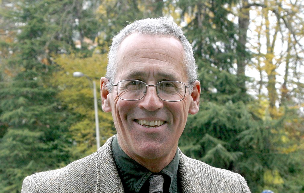 A recent photograph of Joe Butwin, smiling, in suit and tie, with evergreen trees in the background