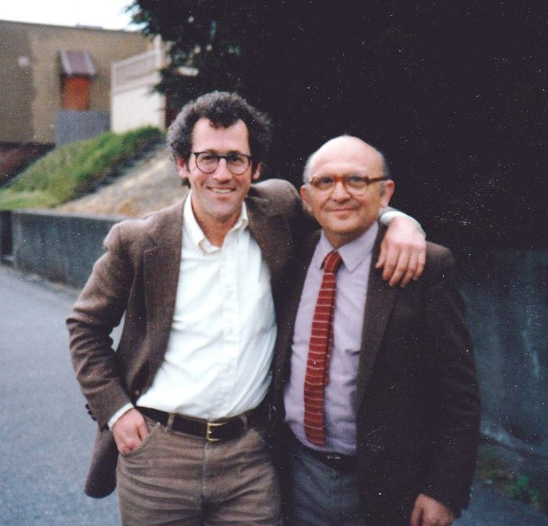A photograph shows Butwin and Appelfeld, wearing suits and glasses. Butwin has his arm around Appelfeld's shoulder. In the background is the Seattle city street.