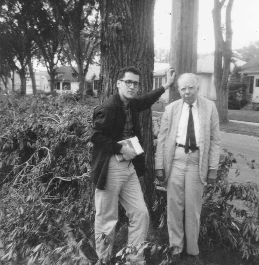 A black-and-white photograph showing Joe Butwin in pants, shirt, suit jacket and glasses, holding a book, alongside an older Dr. Monk, wearing a gray suit and tie, standing in front of a tree and bushes, houses behind