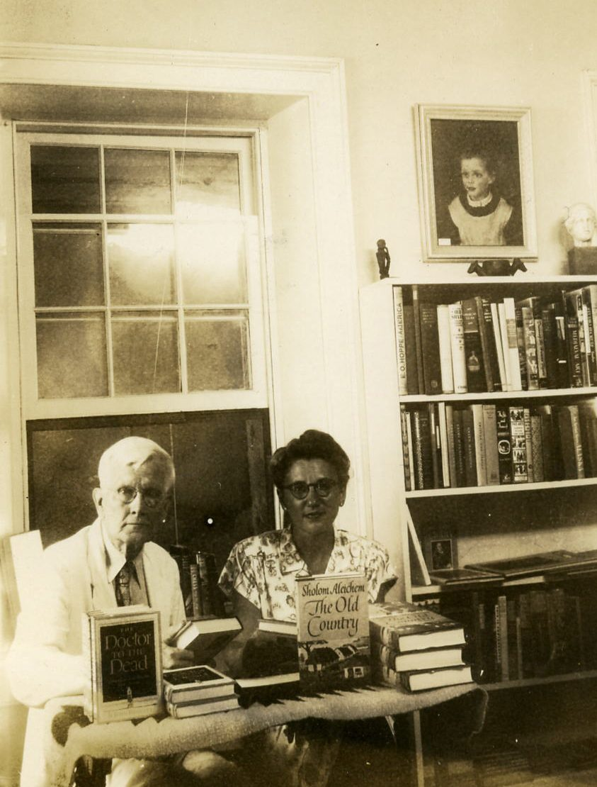 "A black-and-white photograph shows a middle-aged Frances Butwin, hair up, in glasses and a blouse, sitting at a table stacked with books: Sholom Aleichem's ""The Old Country"" and ""Doctor to the Dead"" by John Bennet. Author John Bennet, wearing a white suit, tie and glasses, sits next to her."