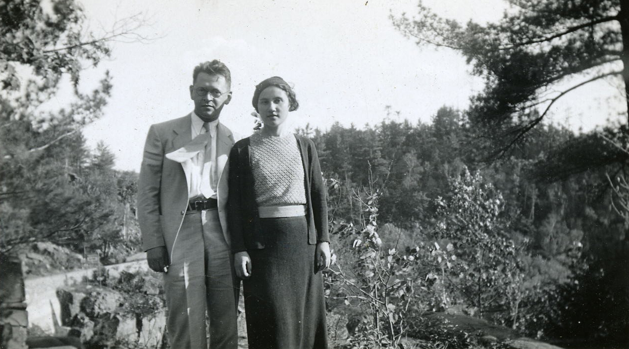 A black-and-white photograph showing Julius, in a suit, tie and glasses, standing next to Frances, wearing a blouse, sweater, skirt and hat. An evergreen forest and trail is visible in the background.