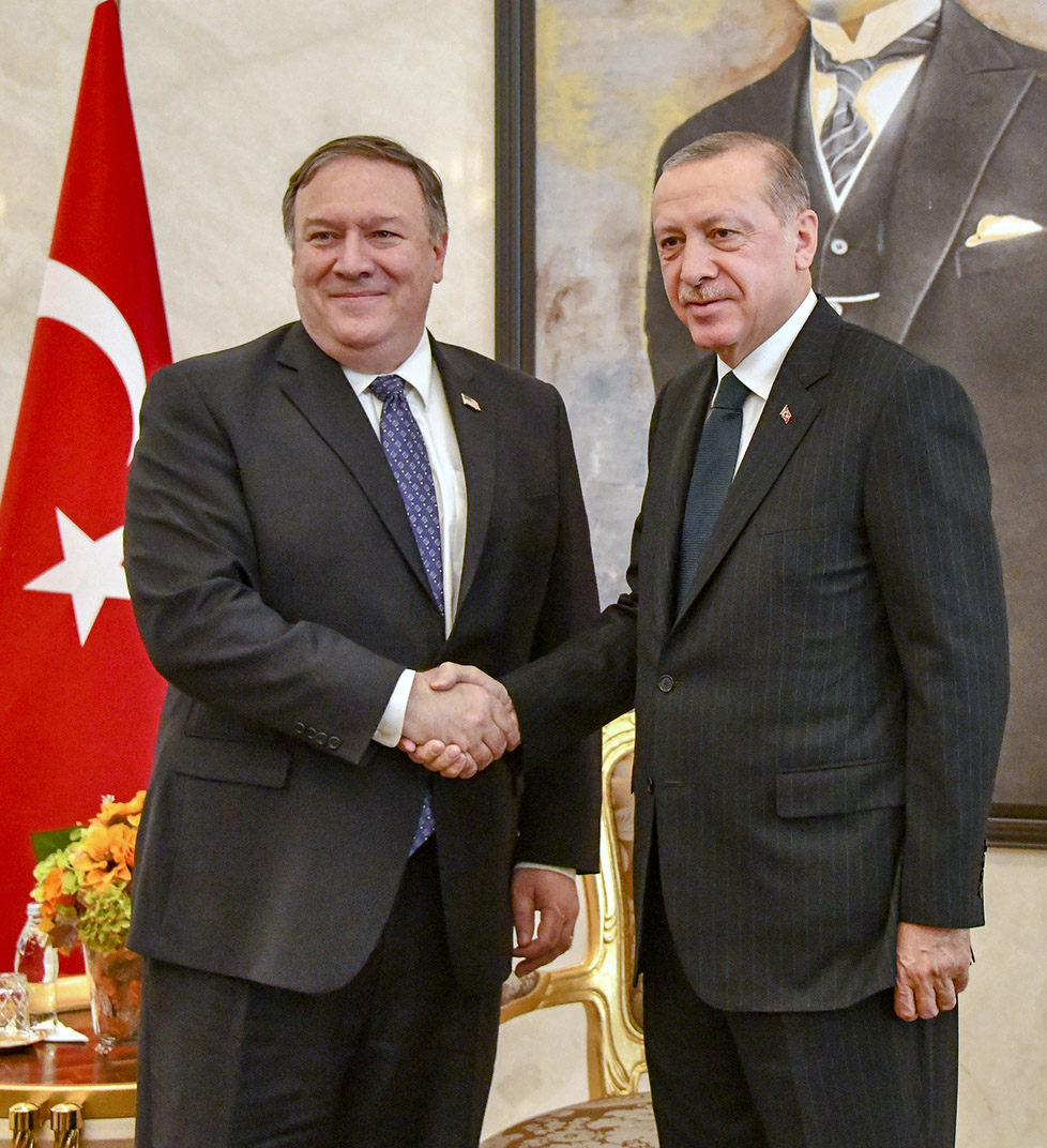 Mike Pompeo shakes hands with President Erdoğan, both in suits, in a hall, with a red Turkish flag and painting behind them