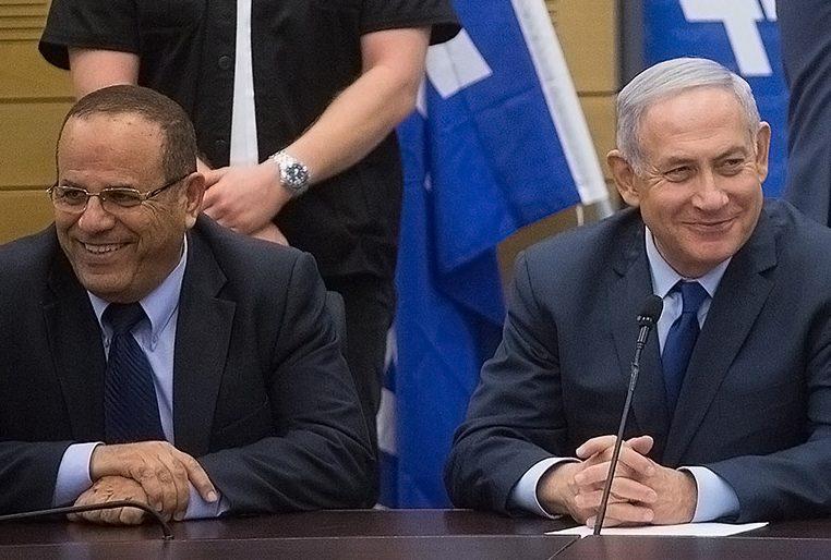 Benjamin Netanyahu sits at table alongside Ayoub Kara, smiling in front of a microphone.