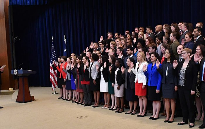 Several dozen employees in formal attire hold their right hands up, taking a pledge onstage in front of Secretary George Pompeo, in suit and tie.