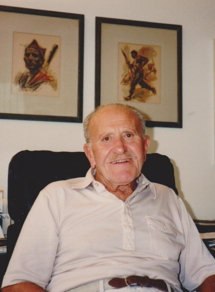 A color photograph of Ed Lending, an older man in a white button-up-shirt, sitting in a chair, with paintings of the Spanish Civil War on the wall