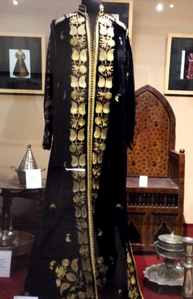 Museum display window showing a black, floor-length, long-sleeved caftan with gold leaf pattern along the edges. Traditional silver serving dishes are in the background, along with wooden wedding chairs decorated with eight-pointed stars