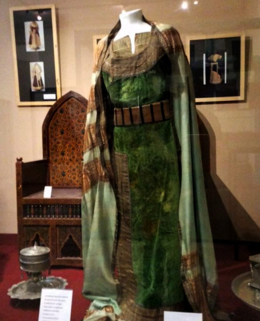 Green wedding dress with a long green shawl and belt. In the background, a wooden wedding chair decorated with a pattern of eight-pointed stars and pictures of dresses hanging on the wall