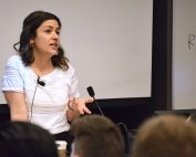 Hadar Khazzam-Horovitz standing at a podium in a full lecture hall