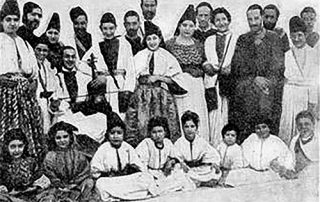 Black and white photograph showing a large group of Moroccan Jews of all ages smiling and wearing traditional clothing: long robes and dresses, shawls, and cylindrical or triangular hats