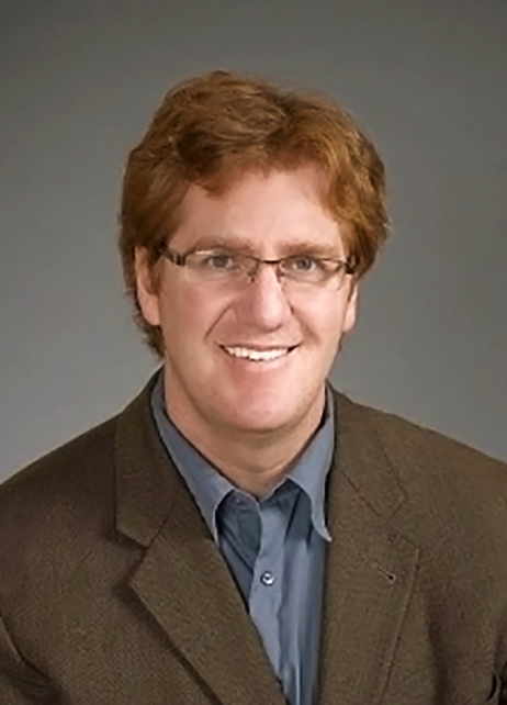 Portrait of Joel Walker in button-up shirt and blazer, with a gray studio background