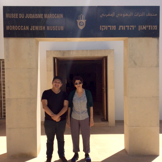 "Author Pablo Jairo Tutillo Maldonado in black shirt and pants standing alongside museum curator Zhor Rahihil, wearing blouse, shawl, and khaki pants outside of the museum entrance with sandstone pillars. A black marble marquee reads ""Moroccan Jewish Museum"" in French, English, Arabic and Hebrew text."