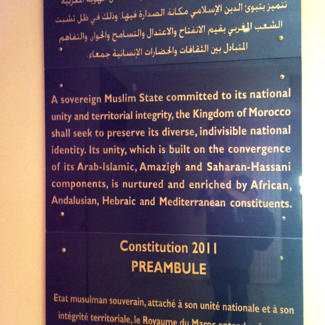 "Black marble plaque showing the 2011 Moroccan constitution preamble in Arabic, English, and French. It reads: ""A sovereign Muslim state committed to its national unity and territorial integrity, the Kingdom of Morrocco shall seek to preserve its diverse, indivisible national identity. Its unity, which is built on the convergence of its Arab-Islamic, Amazigh and Sarahan-Hassani components, is nurtured and enriched by African, Andalusian, Hebraic and Mediterranean constituents."