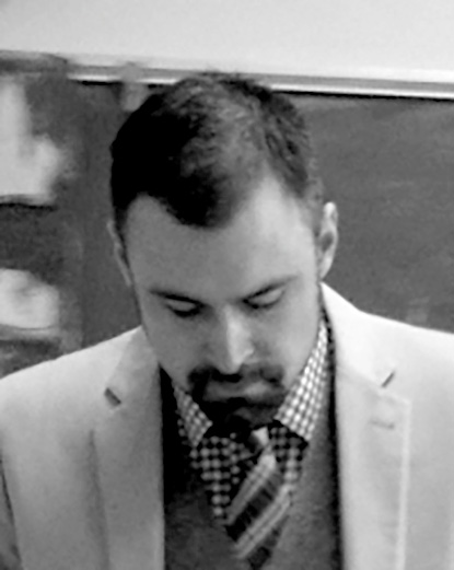 Black-and-white photo of Nicolaas Barr wearing a suit in a classroom, looking downwards