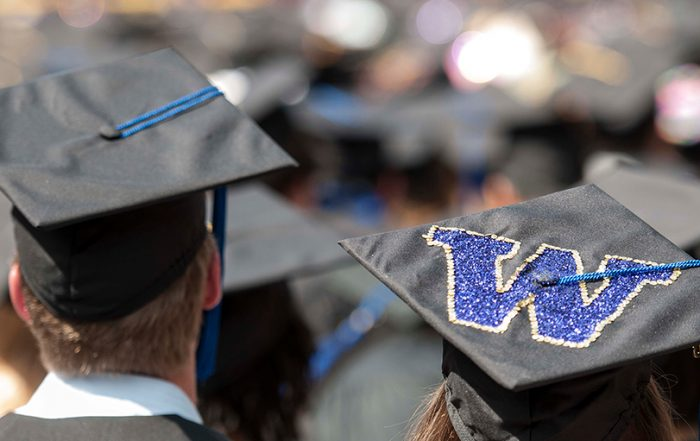 UW graduates stand during commencement, wearing mortarboards that display the purple