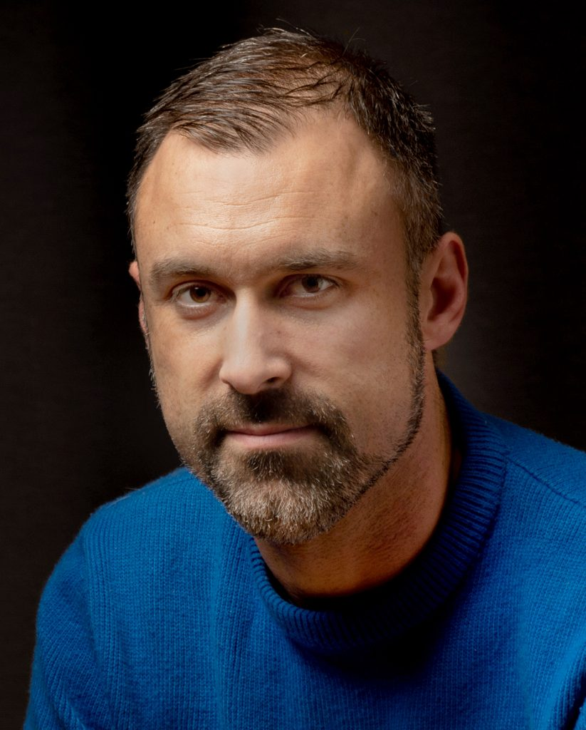 Studio portrait of Nick Barr wearing a sweater, looking serious