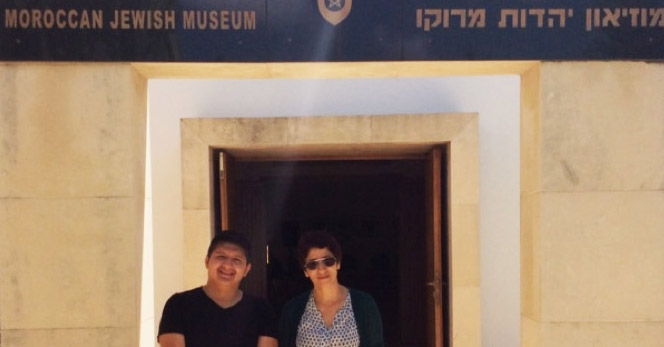 """Author Pablo Jairo Tutillo Maldonado in black shirt and pants standing alongside museum curator Zhor Rahihil, wearing blouse, shawl, and khaki pants outside of the museum entrance with sandstone pillars. A black marble marquee reads """"Moroccan Jewish Museum"""" in French, English, Arabic and Hebrew text."""