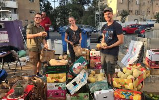 Food frive volunteers, including author Marissa Gaston, stand smiling in front of boxes of produce. A city street, buildings, and trees are visible behind them.