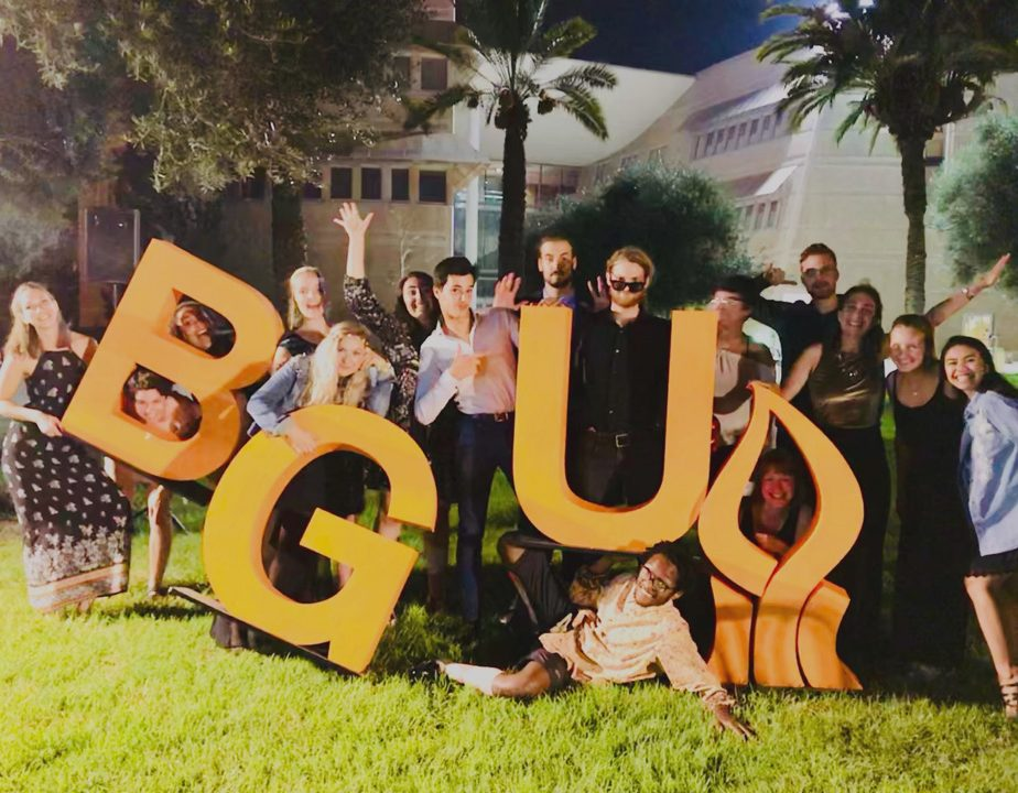 "Smiling students in formal clothing stand on a lawn in front of a large university building at night, holding large yellow letters ""BGU"" and the BGU flame logo"