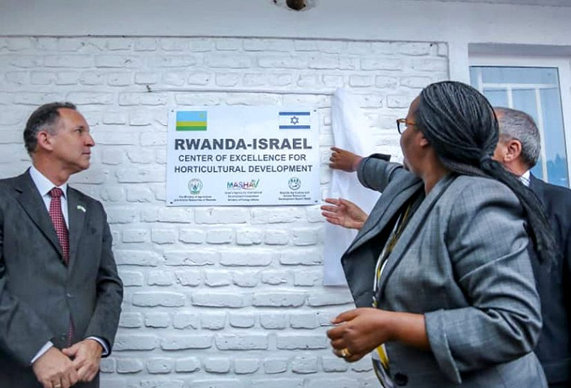 "Gil Haskel, wearing a suit and tie, stand alongside a sign reading ""RWANDA-ISRAEL Center of Excellence for Horticultural Development"" with Minister Mukeshimana in suit and another official gesturing towards it"