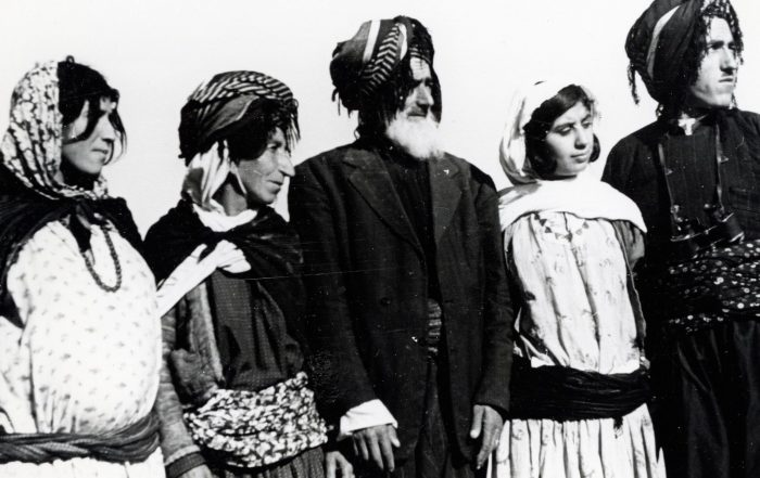 A black-and-white photograph of family members standing in a line, wearing traditional clothing: robes, turbans with tassels and headscarves