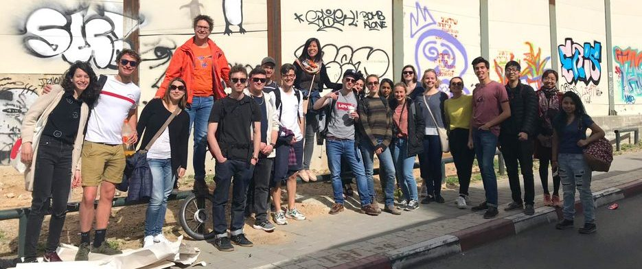 A group of twenty students stands in front of a light wall covered in graffiti, smiling