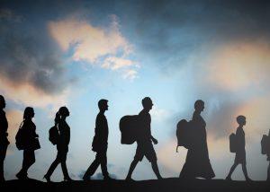 Migrants walking across a field