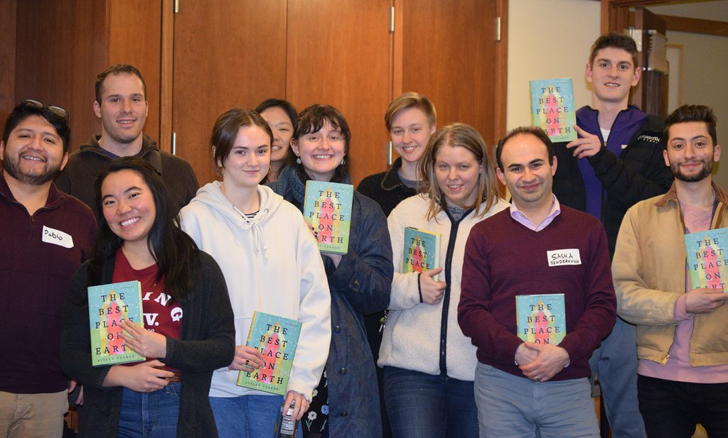 """Group photo showing ten students, smiling and holding copies of """"The Best Place on Earth"""" by Ayelet Tsabari alongside Professor Sasha Senderovich"""