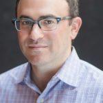 Daniel Schwartz in a button-down shirt and glasses