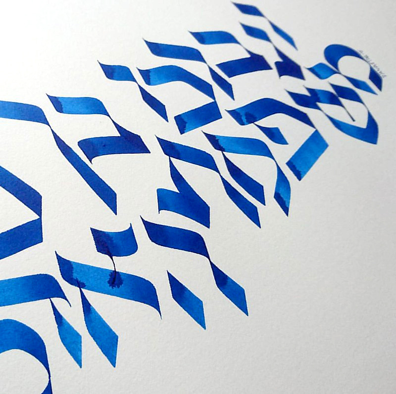 Color photo showing elegant calligraphy with Hebrew letters, made in blue paint on thick paper