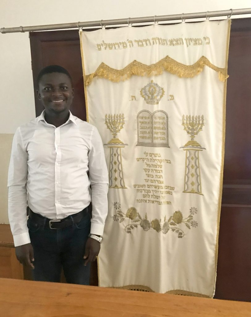 Francis Abugbilla stands alongside an embroidered beige and gold-colored banner in the Etz Hayim congregation. The banner shows the two tablets of the commandments, with Hebrew words inscribed on them, with two menorahs on stands on either side.