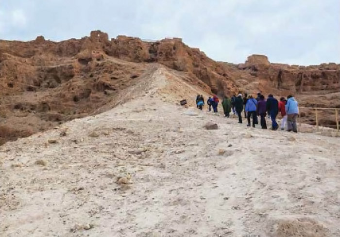 Photograph showing a tour group in contemporary clothing walking along a long dirt road in a rocky desert landscape