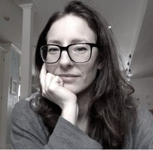 Hillary Kaell wearing glasses with chin resting on hand
