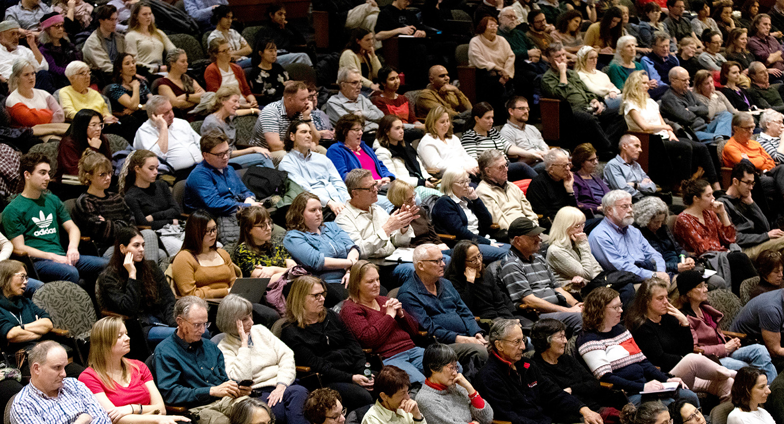 Audience members sitting in a crowded auditorium, engaged