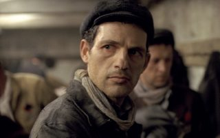 "Photograph from the 2015 film ""Son of Saul,"" showing a grim-looking man frowning, wearing a gray hat, scarf, and heavy coat"