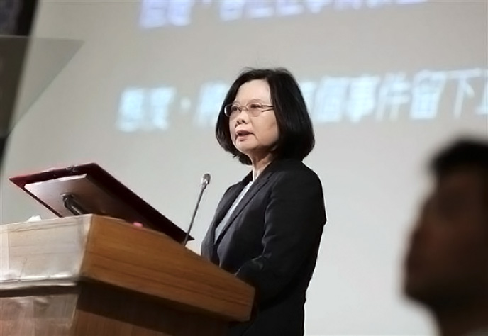 President Tsai stands at a wooden podium, wearing a black blazer and looking serious