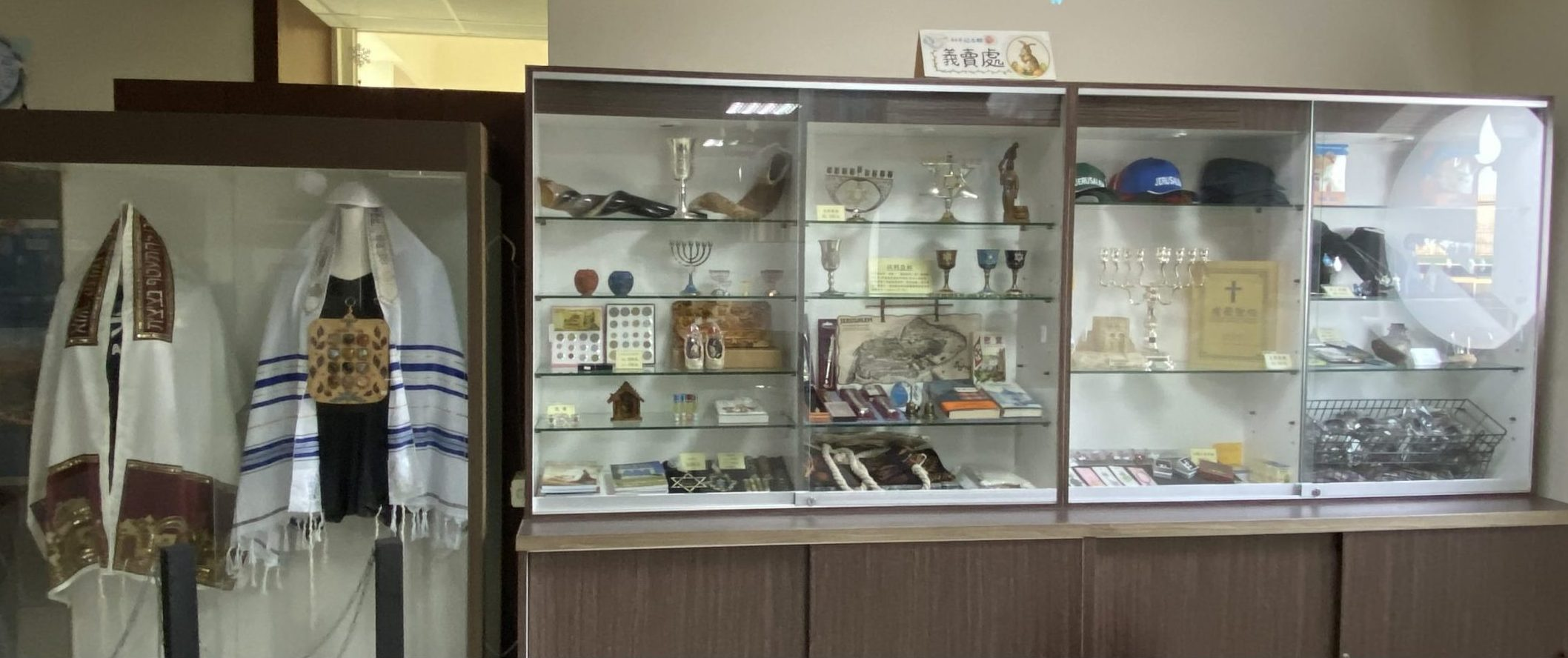 Display cabinets show different kinds of talit (prayer shawls), alongside a smaller items including a shofar (ram's horn trumpet), menorahs, kiddush cups used for wine, and books