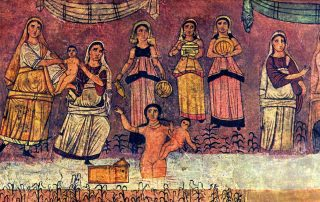 Colorful ancient mosaic shows women in long dresses and head coverings holding babies, as well as water vessels, close to a river