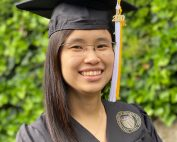 Portrait of Grace Dy smiling, in glasses, wearing a black square graduation cap (mortarboard) and gown, with a white and gold tassel. A verdant hedge is visible in the background.